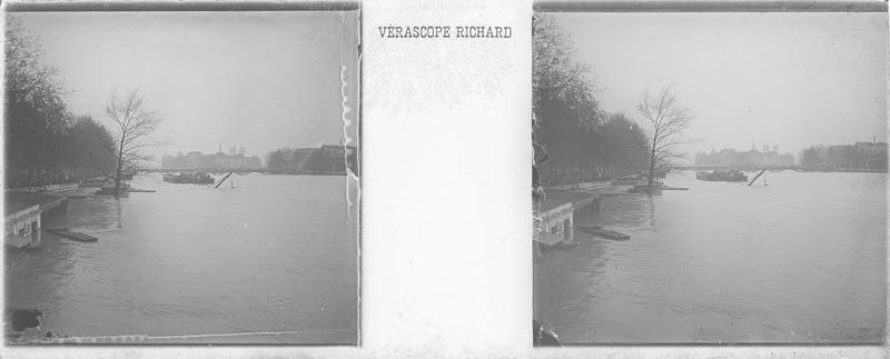 Crue de la Seine : quai inondé et bateau depuis le Pont du Carroussel, et pont des Arts en arrière-plan