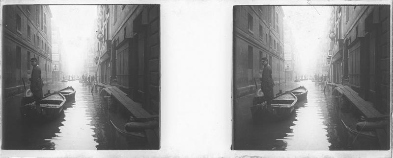 Crue de la Seine : façades sur rue inondée, vue animée avec policier au premier plan, barques et passerelles en bois