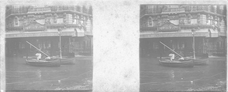 Crue de la Seine : façade sur rue inondée, vue animée avec deux hommes sur des barques