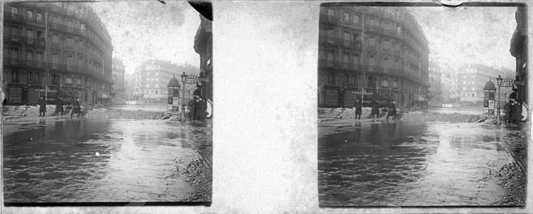 Crue de la Seine : façades sur rue inondée avec barrages au milieu de la chaussée, vue animée