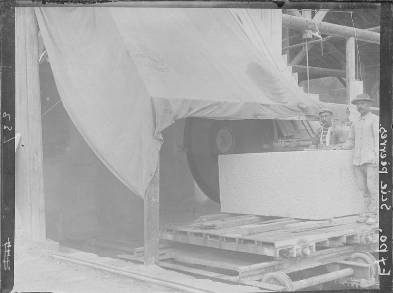 Ouvriers posant à côté d'un bloc de pierre dans un atelier équipé d'une grande scie circulaire