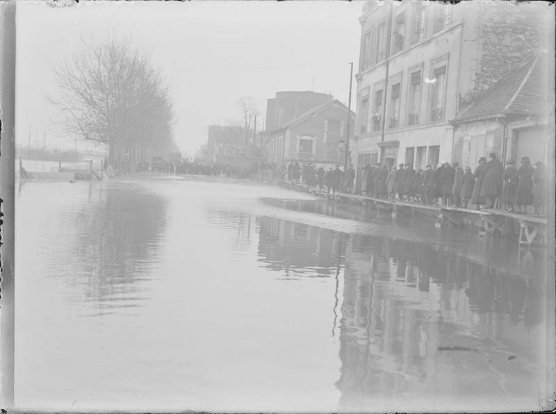 Crue de la Seine : façades sur quai inondé, vue animée avec foule longeant les maisons sur une passerelle en bois