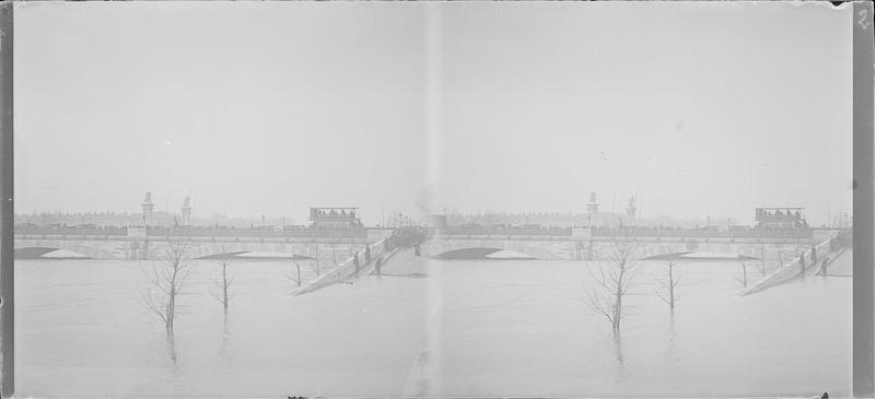 Crue de la Seine : quai inondé et pont des Invalides depuis le Cours Albert Ier, vue animée avec foule observant la montée des eaux et bus