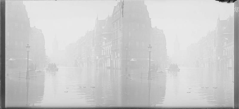 Crue de la Seine : façades sur rue inondée et gare de Lyon en arrière-plan