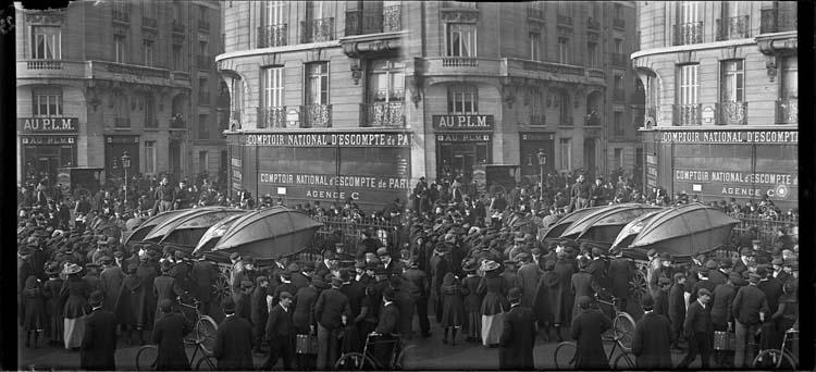 Crue de la Seine : façades sur rue, vue animée avec foule autour d'une charrette transportant des barques