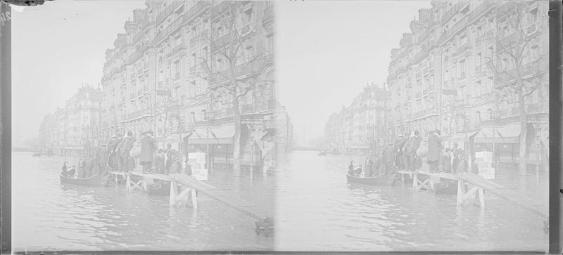 Crue de la Seine : façades sur rue inondée, vue animée avec groupe débarquant sur une passerelle en bois