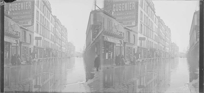 Crue de la Seine : façades sur rue inondée, vue animée avec personnes longeant les maisons sur une passerelle en bois