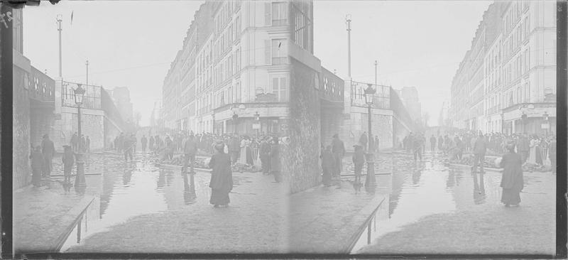 Crue de la Seine : façades sur rue inondée située le long des voies de la gare de Lyon, vue animée avec foule observant les débris sur la chaussée