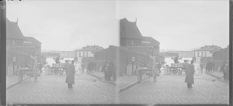 Crue de la Seine : ensemble sur chaussée inondée, vue animée avec hommes chargeant des marchandises sur une charrette