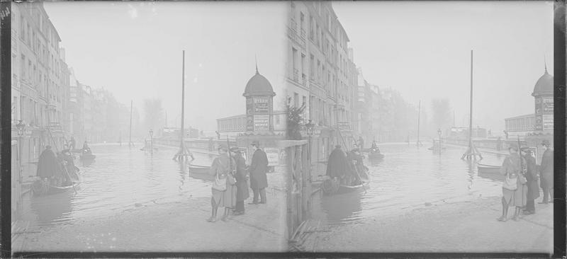 Crue de la Seine : façades sur quai inondé, vue animée avec barques et colonne Morris avec publicité Byrrh et Chocolat Menier