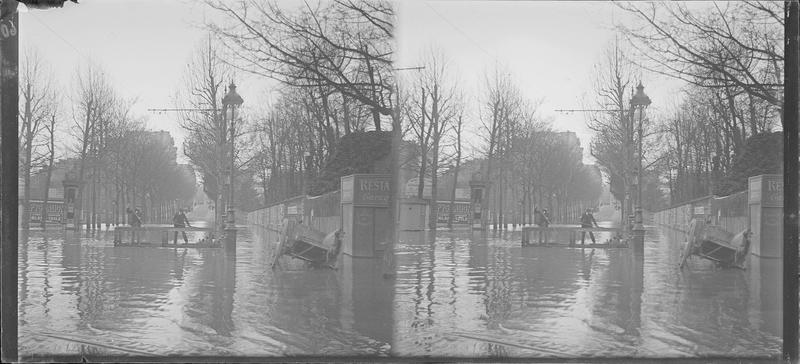 Crue de la Seine : rue inondée, vue animée avec hommes sur une barque et charrette abandonnée sur le trottoir