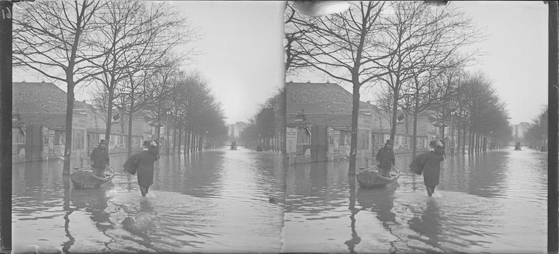 Crue de la Seine : façades sur avenue inondée, vue animée avec homme portant dans ses bras une femme jusqu'à une barque