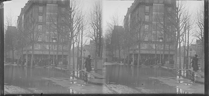 Crue de la Seine : façade sur place inondée, vue animée avec foule longeant la chaussée sur une passerelle en bois