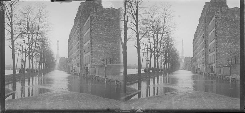Crue de la Seine : façades sur quai inondé et Tour Eiffel en arrière-plan, vue animée avec personnes longeant les immeubles sur une passerelle en bois