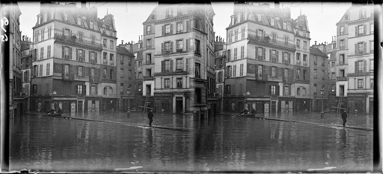 Crue de la Seine : façades sur quai inondé, vue animée avec barque et homme traversant la chaussée sur une passerelle en bois