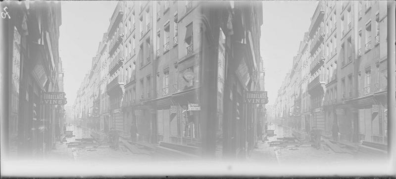 Crue de la Seine : façades sur rue inondée, vue animée avec hommes longeant les immeubles sur des passerelles en bois