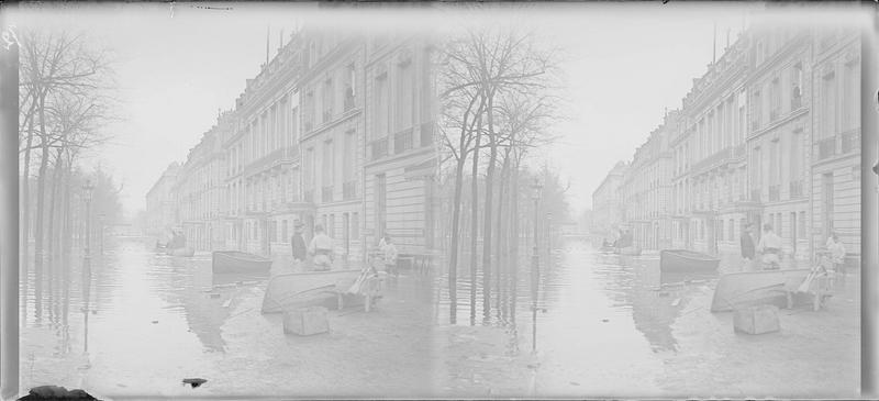 Crue de la Seine : façades sur boulevard inondé, vue animée avec hommes les pieds dans l'eau et barques