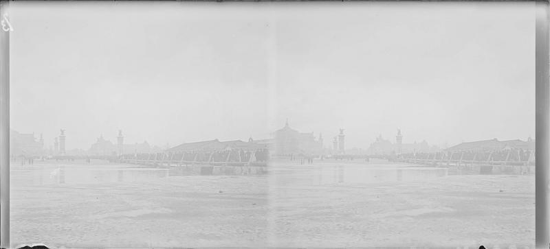 Crue de la Seine : avenue inondée et pont Alexandre III en arrière-plan, vue animée avec foule longeant l'avenue sur une passerelle en bois