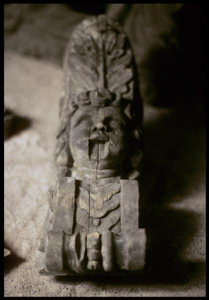 Vue d'un élément de décor en bois à tête de femme.