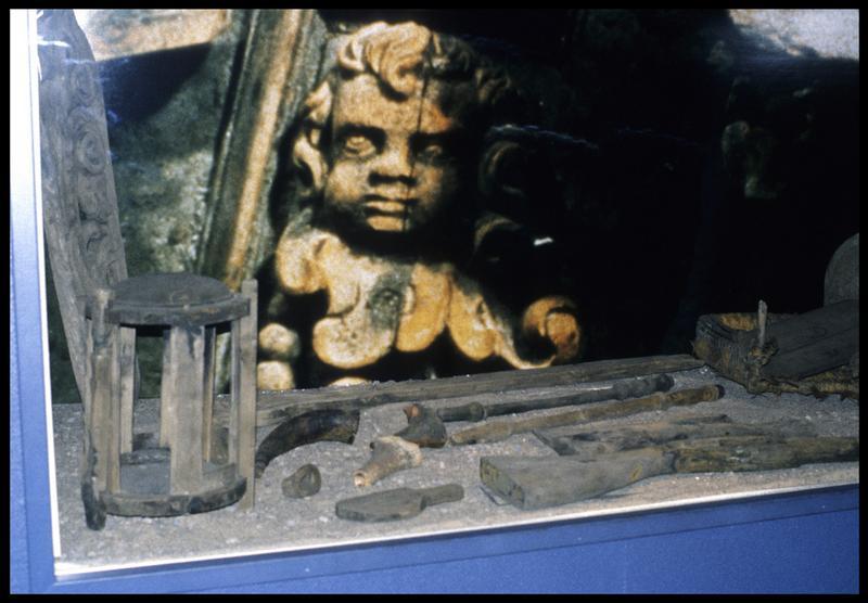 Vue d'une vitrine avec de éléments de bois dont des crosses de fusil.