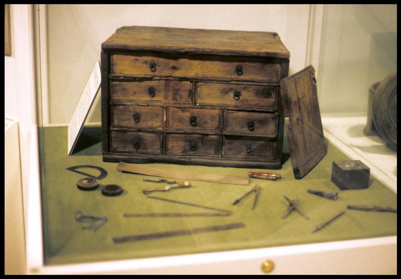 Vue d'un coffret de bois avec des instruments de calcul de navigation (compas, règles...) en métal.