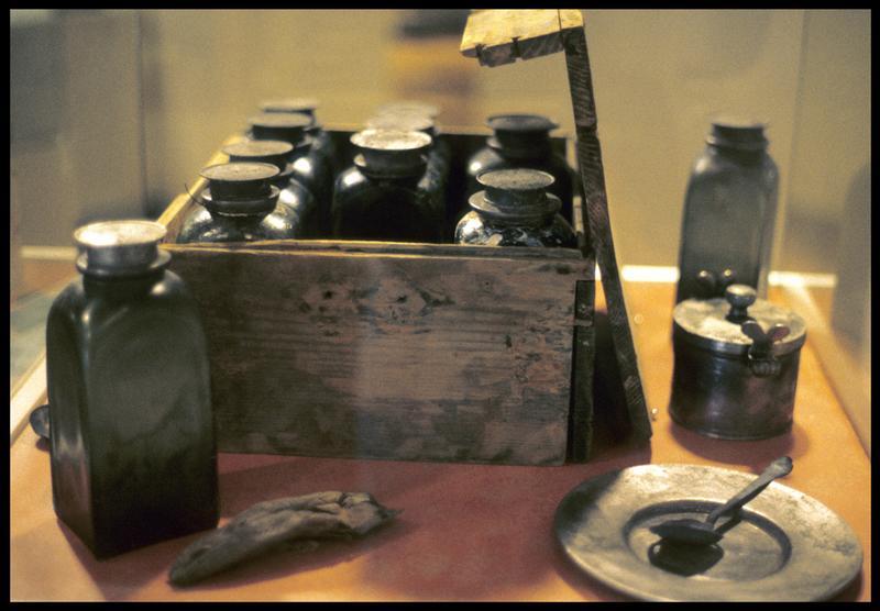 Vue d'une vitrine avec un coffret de bois avec des fioles de verre et assiette et cuillère métallique.