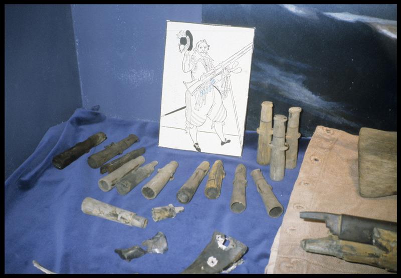 Vue de la vitrine avec des éléments d'armement de fusil.