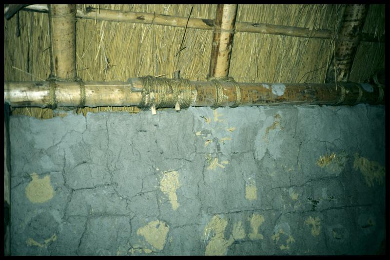 Vue des murs d'une cabane et de la jonction de deux poutres de la charpente.