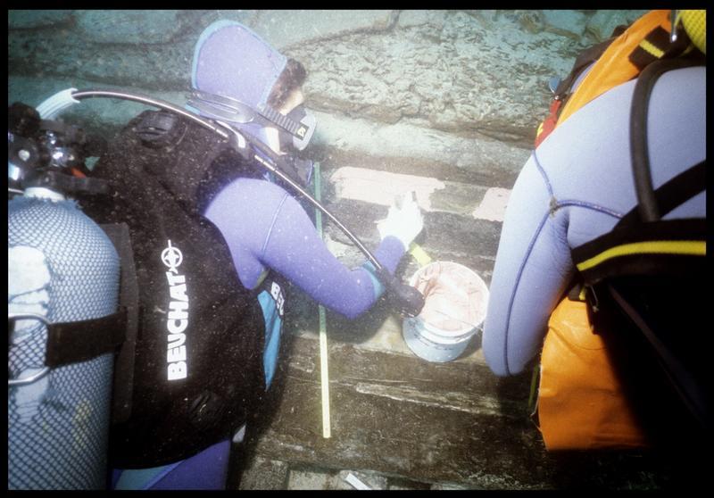 Vue sous-marine de deux plongeurs étalant le silicone sur la carène (fouille S. Ximénès).