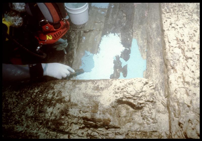 Vue sous-marine d'un plongeur étalant le silicone sur la carène (fouille S. Ximénès).
