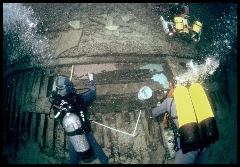 Vue sous-marine de deux plongeurs étalant le silicone de moulage sur la carène (fouille S. Ximénès).