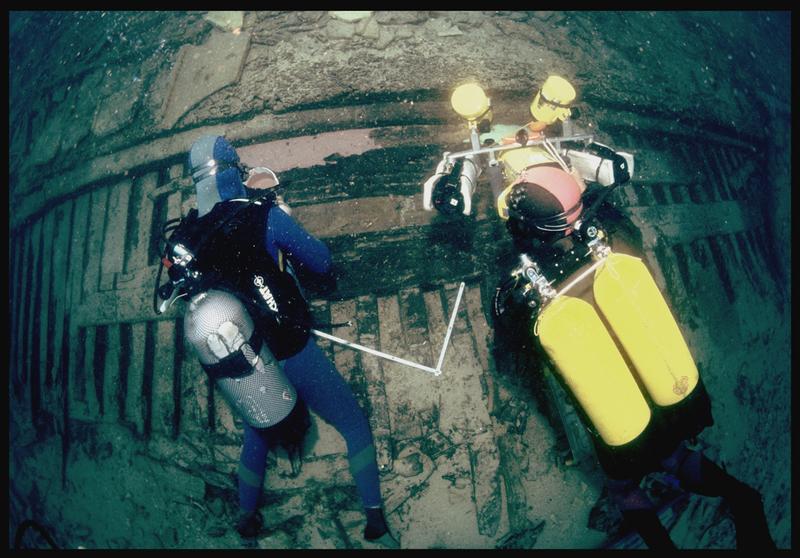 Vue sous-marine d'un plongeur étalant le silicone de moulage sur la carène et d'un vidéaste (fouille S. Ximénès).