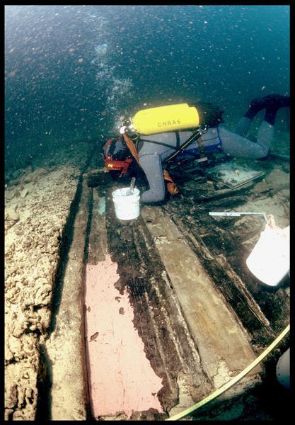 Vue sous-marine d'un plongeur étalant le silicone de moulage sur la carène (fouille S. Ximénès).