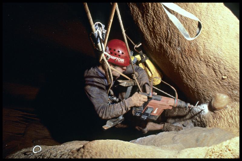 Vue de la mise en place des pitons de l'échelle au Spitgun dans l'accès au grand puits (fouille J. Courtin, J. Clottes).