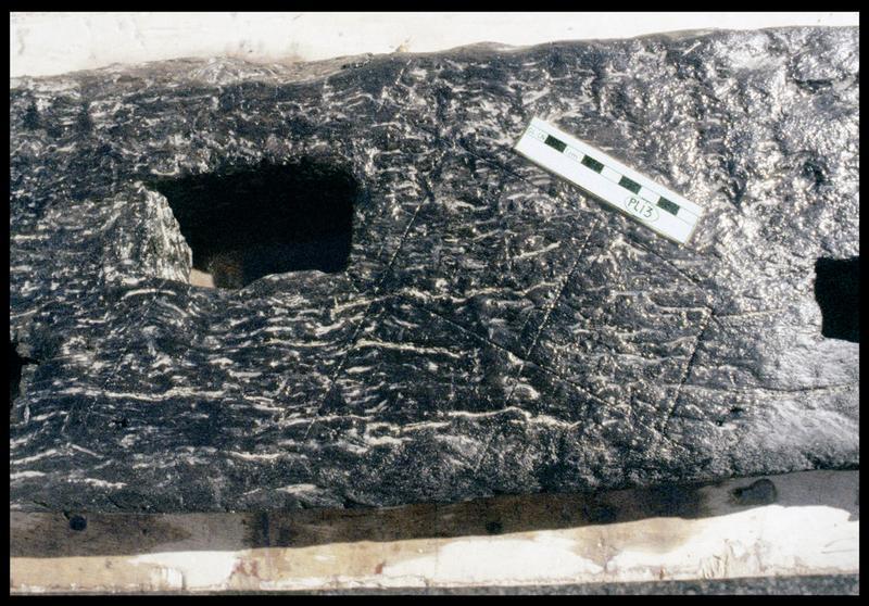 Vue de détail des cavités et des traces d'outils de la pièce PLI3 (fouille E. Rieth).