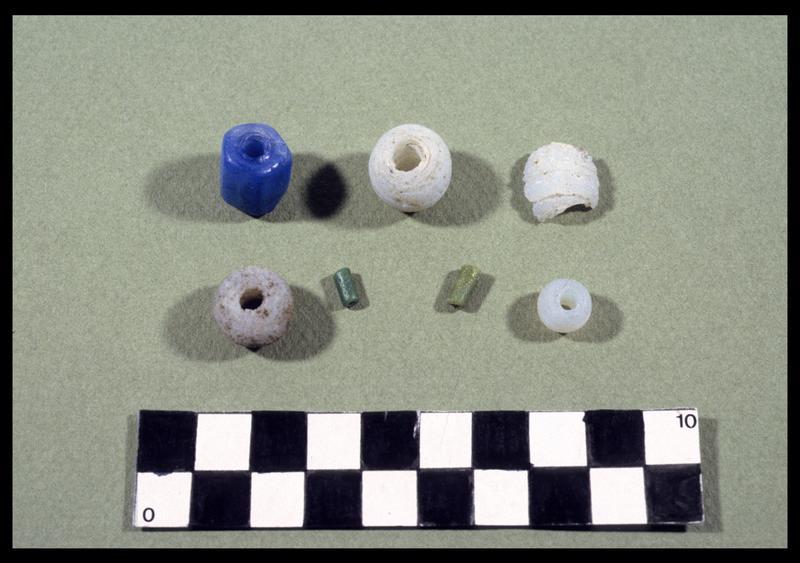Vue de sept perles de verre (quatre blanches, deux vertes, et une bleue) (fouille D. David).