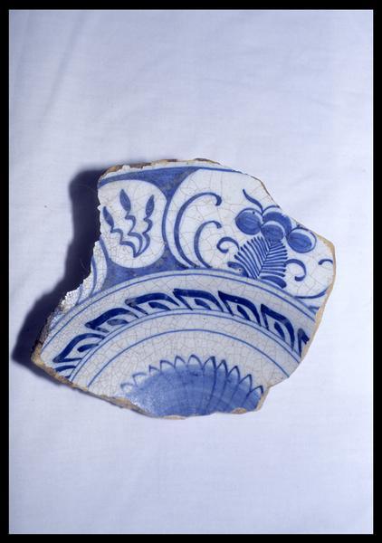 Vue d'un fragment d'assiette de faïence blanche à décor végétal bleu (fouille D. David).