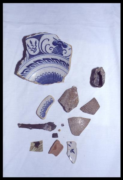 Vue des divers éléments découverts en céramique (grès, faïence et porcelaine), métal (gobelet et cuillère), verre (perles) et bois (dé à jouer) (fouille D. David).