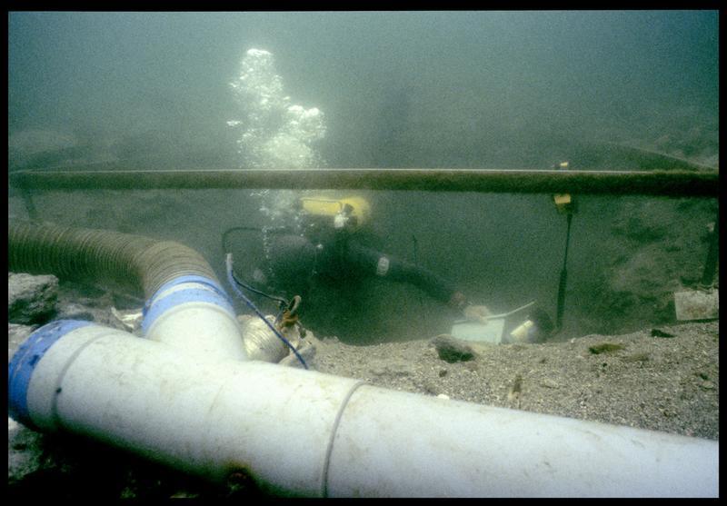 Vue sous-marine d'un plongeur dévasant à la suceuse à eau (fouille F. Leroy/Drassm).