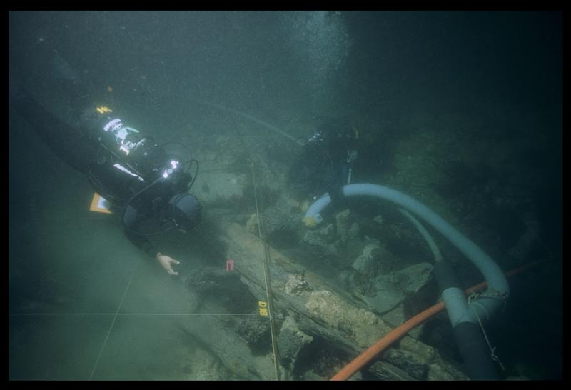 Vue sous-marine de deux plongeurs dévasant à la suceuse à eau la carène (fouille M. L'Hour/Drassm, E. Veyrat/Drassm).