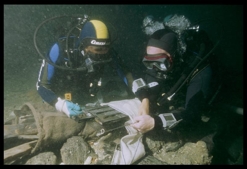 Vue sous-marine de deux plongeurs emballant une pièce de bois fragile (fouille M. L'Hour/Drassm, E. Veyrat/Drassm).