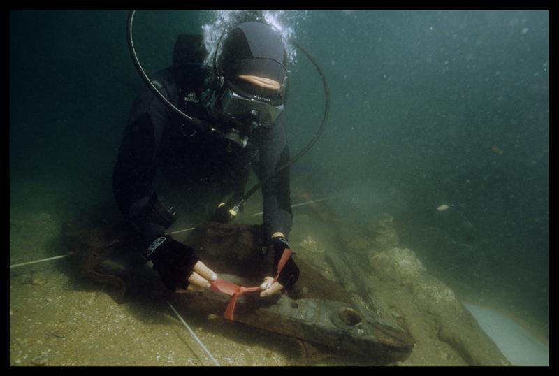 Vue sous-marine d'un plongeur marquant un élément de bois (fouille M. L'Hour/Drassm, E. Veyrat/Drassm).