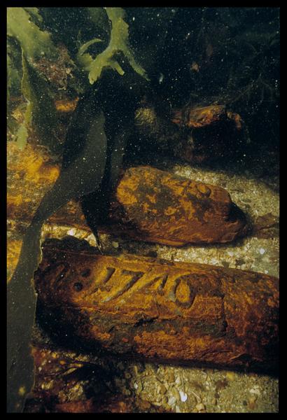 Vue sous-marine de trois lingots de fonte de fer marqués (1746) in situ (fouille M. L'Hour/Drassm, E. Veyrat/Drassm).