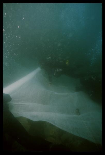 Vue sous-marine de deux plongeurs installant un film protecteur avant de réensablage (fouille M. L'Hour/Drassm, E. Veyrat/Drassm).