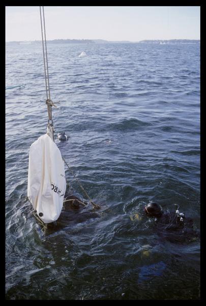 Vue du levage par grue d'un ballon accompagné de deux plongeurs (fouille M. L'Hour/Drassm, E. Veyrat/Drassm).