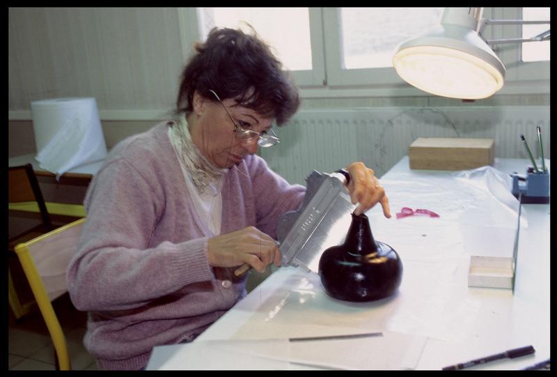 Vue du travail de la dessinatrice sur une bouteille de verre (fouille M. L'Hour/Drassm, E. Veyrat/Drassm).