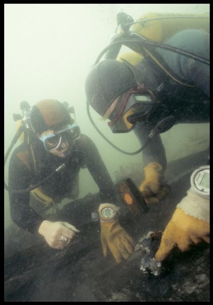 Vue sous-marine de deux plongeurs effectuant un prélèvement sur la carène (fouille M. L'Hour/Drassm, E. Veyrat/Drassm).
