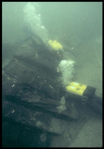 Vue sous-marine de deux plongeurs effectuant le relevé de la carène (fouille M. L'Hour/Drassm, E. Veyrat/Drassm).