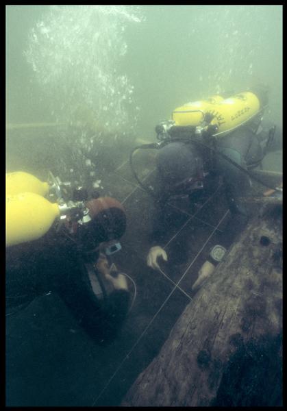 Vue sous-marine de deux plongeurs effectuant le carroyage sur la carène (fouille M. L'Hour/Drassm, E. Veyrat/Drassm).