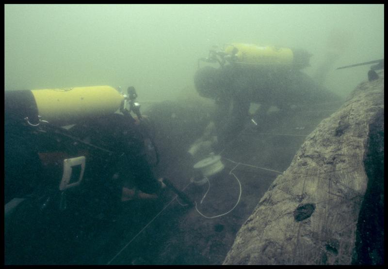 Vue sous-marine de deux plongeurs mettant en place le carroyage sur la carène (fouille M. L'Hour/Drassm, E. Veyrat/Drassm).